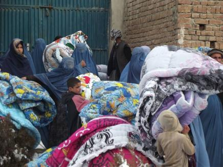 Distributing duvets in a refugee camp