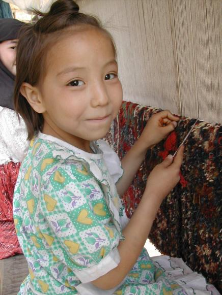 Afghan children weaving carpets