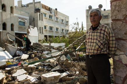 Ahmed Suleman Ateya standing next to his destroyed home in Gaza: Photo-Johnny Barber