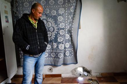 The father of Fares stands near where the shrapnel penetrated his home and decapitated his son.