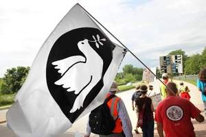 Jules Orkin from Bergin Field, N.J., holds a flag with a peace dove on it while protesting Saturday on Mormon Trek Boulevard en route to Kent Park. More than a dozen demonstrators are marching 195 miles from Rock Island to Des Moines. / Ben Roberts