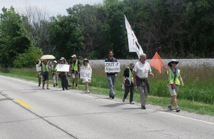"""Covering ground to ground the drones"" is the theme of a group's planned 190-mile march from the Rock Island Arsenal to Des Moines. By noon Tuesday the 13-member group had walked along Iowa Highway 22 nearly to Fairport."