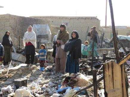 Refugees in the Chaman e Babrak camp stand amid the rubble: photo by Abdulai Safarali